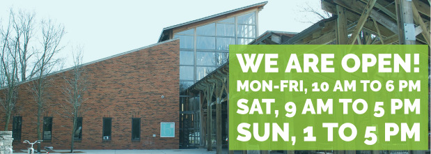 Image of library building with new temporary hours, monday - friday, 10 AM to 6 PM, saturday 9 AM to 5 PM, sunday, 1 to 5 PM